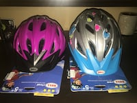 two grey and pink Bell bicycle helmets