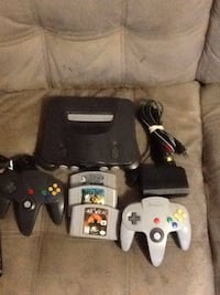 black Nintendo 64 console with controller and game cartridge
