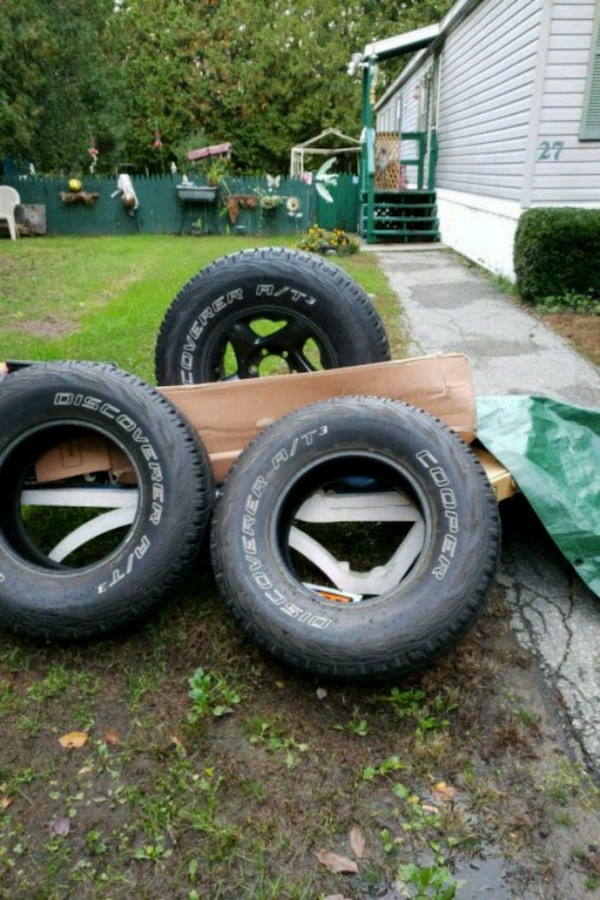 four black vehicle tires with wheels