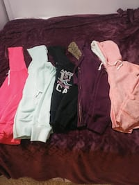 five assorted colors and brands of pullover hoodies