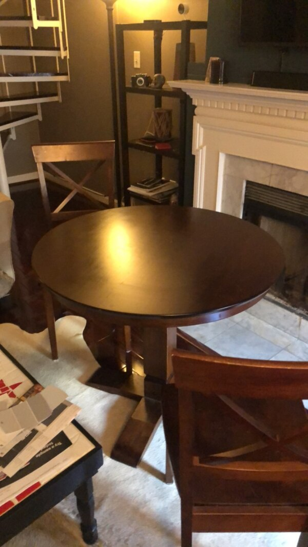 Round brown wooden table with two chairs dining set