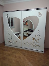 white wooden closet with heart shape mirror