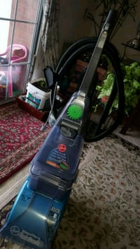 black and green Bissell upright vacuum cleaner