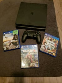 black Sony PS4 with controller and game cases Laval, H7N 2T5