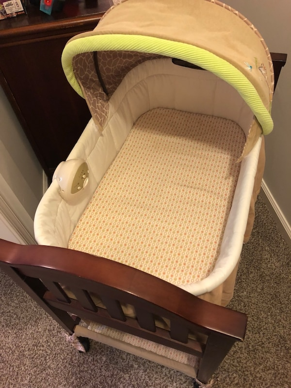 Baby bassinet with folding cover, music and vibration attachment, mat with cover, and bottom storage shelf