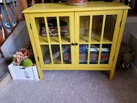 yellow wooden framed glass display cabinet