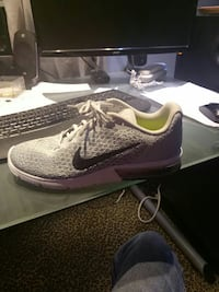 unpaired gray Nike low-top sneaker and computer keyboard