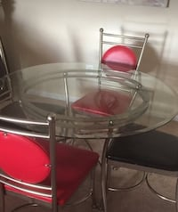 round clear glass top table with four chairs Alexandria