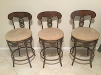 Three brown wooden framed white padded chairs