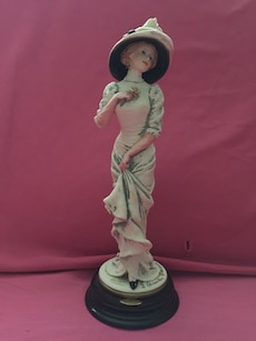 female holding rose to it's heart with other hand on skirt ceramic figurine