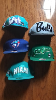 five blue, green, and grey fitted caps