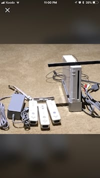 white Nintendo Wii with three remotes and one gray power brick screenshot Edmonton, T6X 1L2