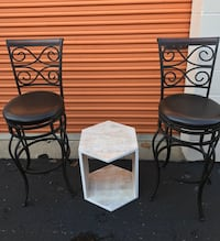 Brown Leather like barstools with cream and beige accent table.