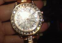 round gold-colored analog watch with link bracelet