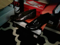 women's pair of black leather flat shoes on box