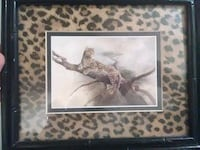 black framed leopard on tree branch painting