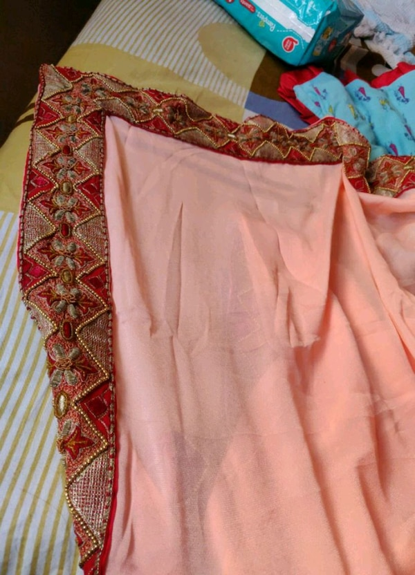 women's peach with red border Saree....