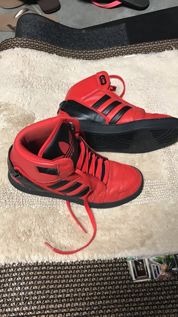 Pair of red and black adidas high top sneakers