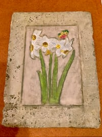 Stone hanging piece with daffodils and a butterfly
