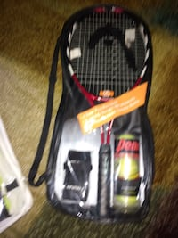Red and black Head lawn tennis racket one men's andbone woman's. New