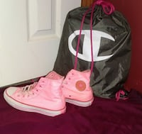 pair of pink Converse All Star high tops and black Champion drawstring backpack