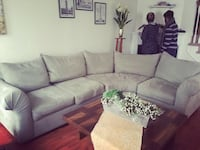 Green suede sectional sofa with throw pillows