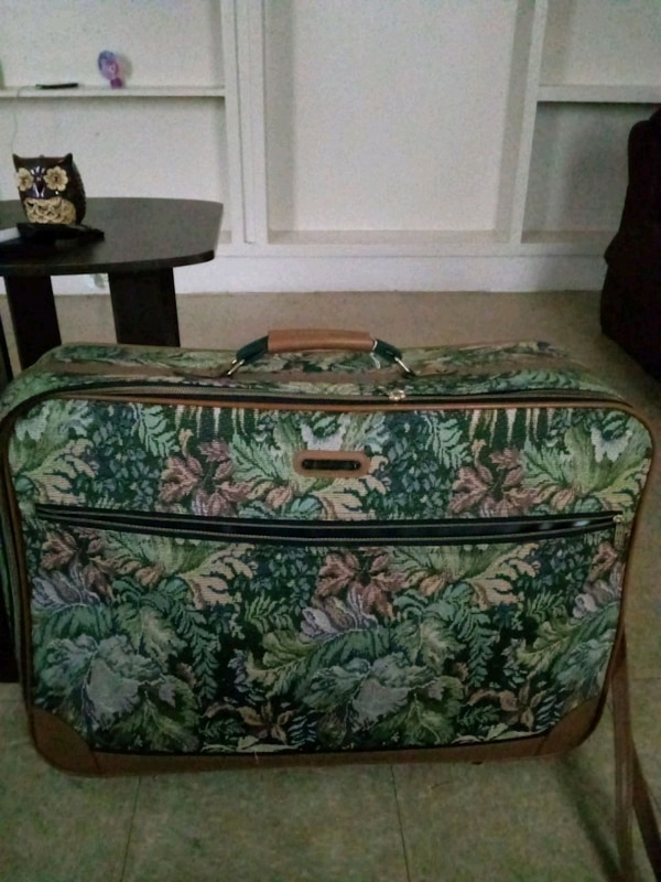 green and white floral luggage bag