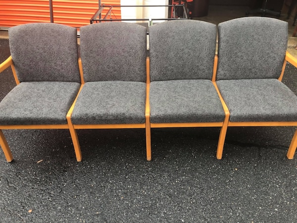 two brown wooden framed gray padded armchairs
