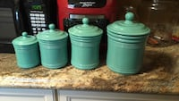 Four teal ceramic canisters with lids