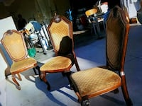 three brown wood-framed beige padded chairs