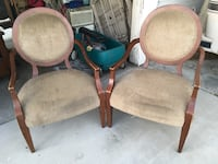 two brown wooden framed padded armchairs