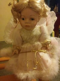 Porcelain doll in pink dress and pillow
