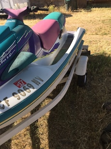 teal and white Yamaha personal watercraft