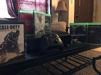 black Xbox One console with controller and game cases Denver, 80203