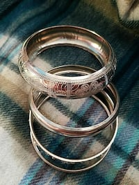 four gold-colored embossed bangles