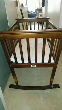 baby's brown wooden crib (Jolly Jumper)