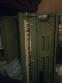 green and white upright piano