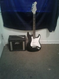 black and white stratocaster electric guitar with amplifier