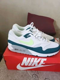 pair of white-and-green Nike running shoes