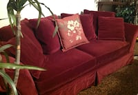 Red velvet couch with pillows