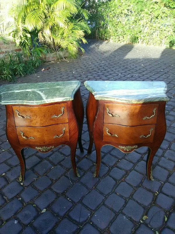 two brown wooden 2-drawer footed chests
