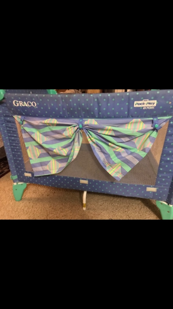 blue and green floral travel cot