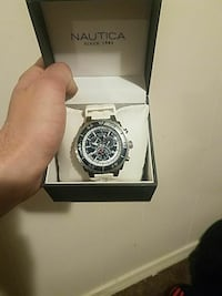 round black chronograph watch with silver link bracelet and box