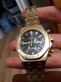 black and gold chronograph watch with gold link bracelet