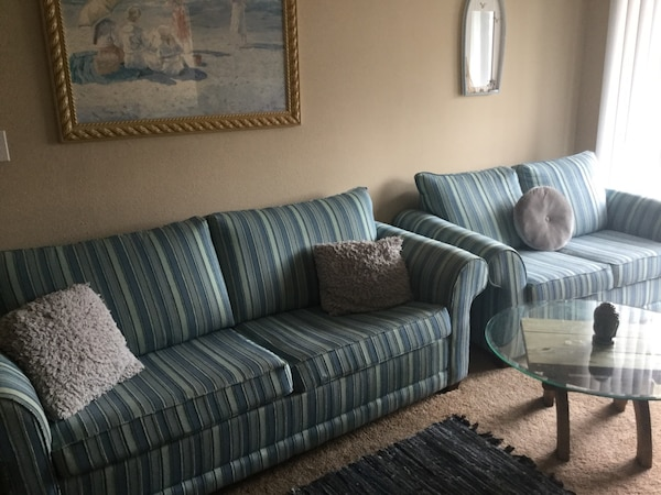 Blue striped sofa set with fold out queen bed.