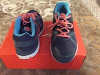 Pair of gray-and-blue nike running shoes with box
