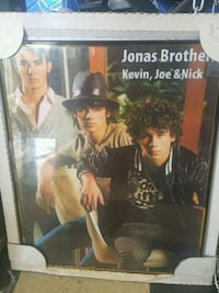 black framed Jonas Brothers poster