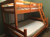 brown wooden bunk bed with mattresses