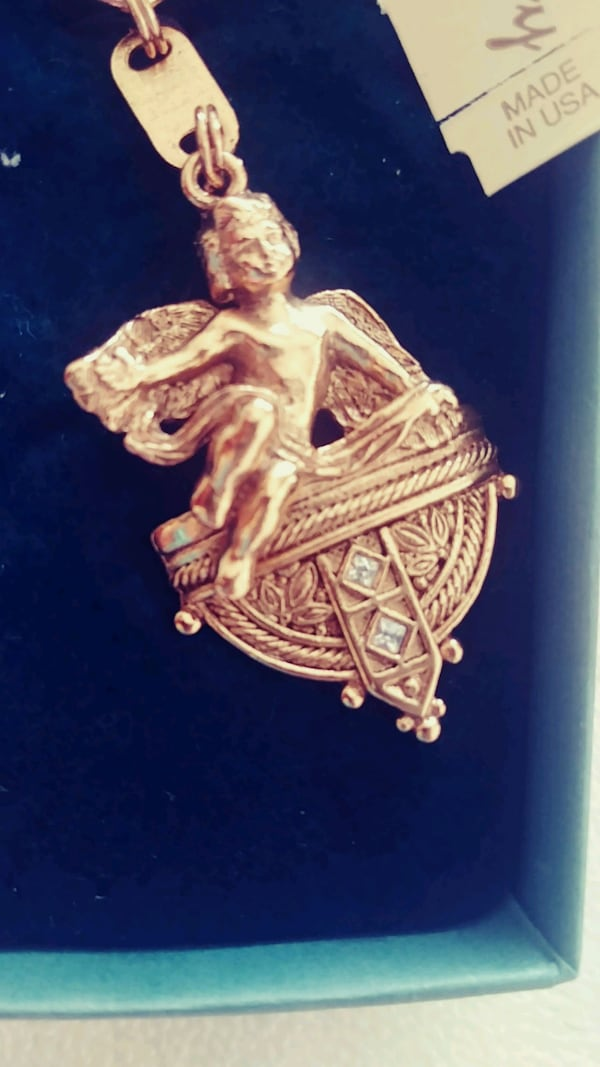 A keychain with a angel and gold color  7e033236-61fd-46a6-8a72-255d15557e62