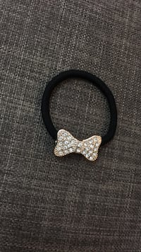 black rope bracelet with diamond encrusted gold-colored bow charm pendant